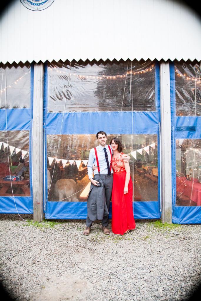 Red wedding dress on bride and groom hugging during Peaks Island wedding in Maine.